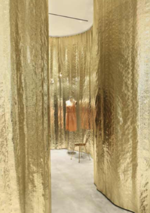 Detail of a store section with golden walls and a mannequin inside
