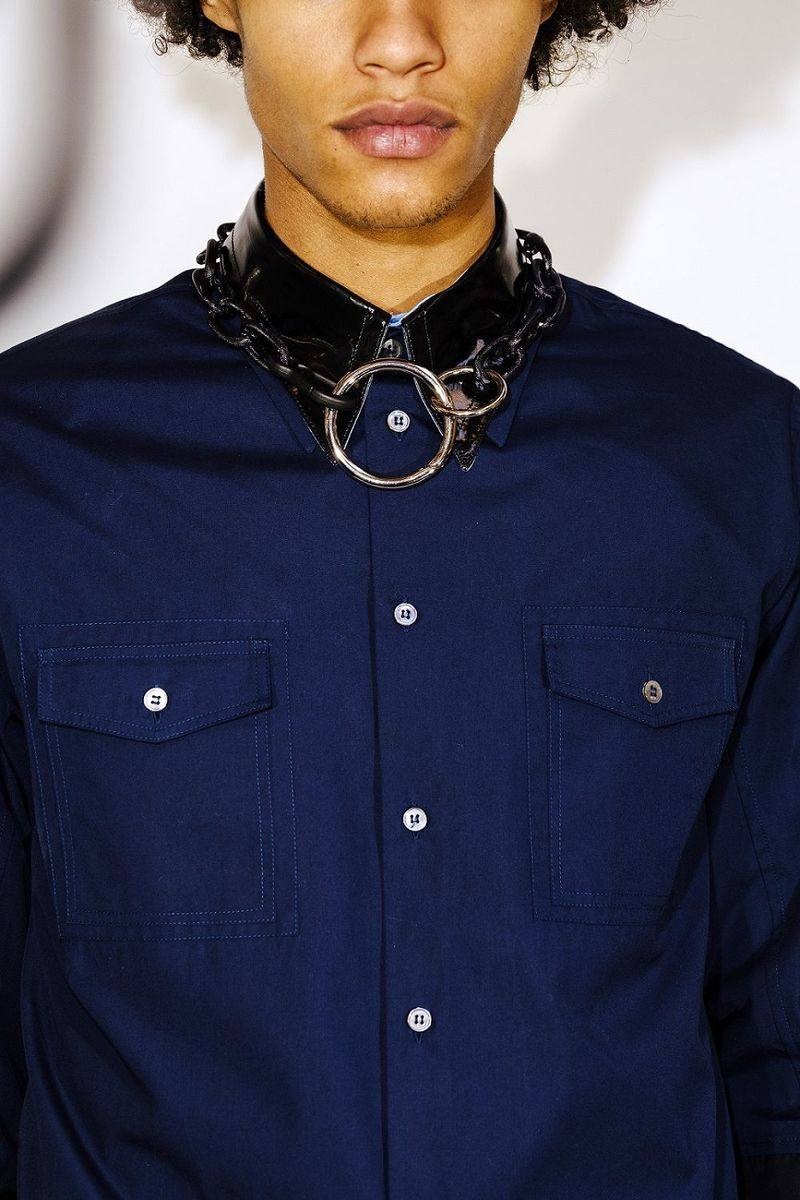 Male model with blue shirt and chain accessory